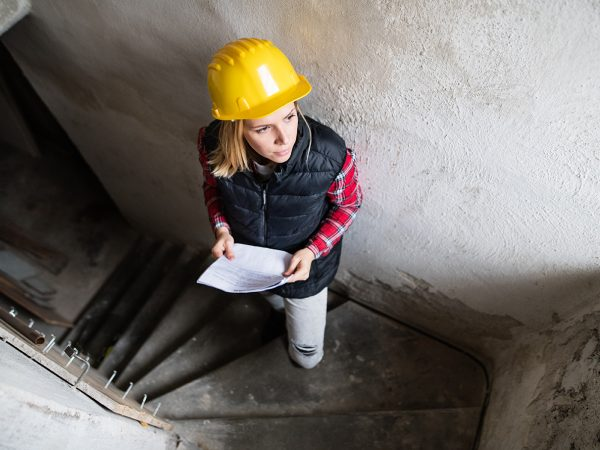 Female worker on the building site. Beautiful young woman holding blueprints. House construction. Top view.